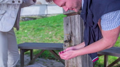 Man drinking water from wooden fountain Stock Footage