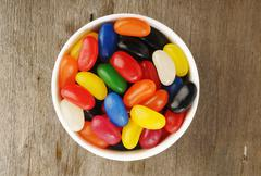 Jelly Beans in a bowl on wooden - stock photo