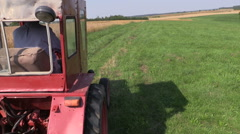 Farmer drive red old tractor between farm rural fields Stock Footage