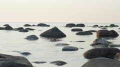 Large boulders on a rocky beach, calm sea, evening light - stock footage