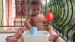 Small boy plays with water and kitchen ware- Stock Footage