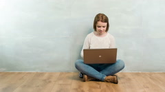 Pleasant woman sitting cross-legged with laptop - stock footage