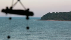 Distant island at the sea with wind chimes swinging in the foreground Stock Footage