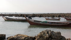 Small boats float attached to ropes at a local shore in Thailand Stock Footage
