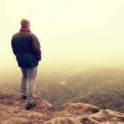 Melancholy and sad day. Man at enge of rock above deep vally.  Tourist on the - stock photo