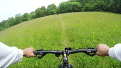 First person view of a cyclist speeding through a path in a lush green field Stock Footage