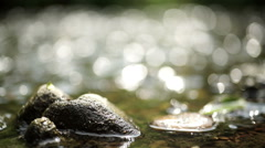 sunlight on stones and water. - stock footage