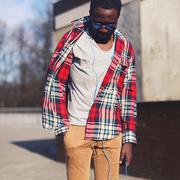 Street fashion concept - portrait of stylish young african man standing liste - stock photo