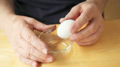 Man with finger tremor separates egg Stock Footage