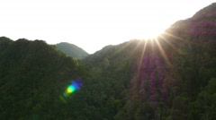 Fly down aside forestry mountain, bright sundisc, shaded by mountain Stock Footage