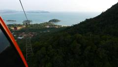 View from within cable car moving down, rainforest mountain in deep shadow Stock Footage