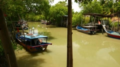 Tropical river, green turbid water, fishing boats parked on sides, pan shot Stock Footage