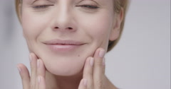 Beautiful healthy woman touching smooth skin on face in slow motion for beauty - stock footage
