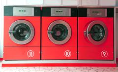 Three red washing machines in coin laundry Kuvituskuvat