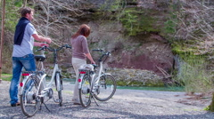 Couple arrives with electric bicycles to the creek Stock Footage