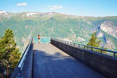 Stock Photo of Woman enjoying scenics from Stegastein Viewpoint