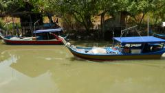 Fishing motor boat on green muddy canal, tracking shot Stock Footage