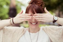Playful Lady Covering her Eyes Using her Hands - stock photo