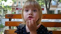 Cute little girl face grimace while sitting on a bench - stock footage