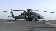 Green Shirts Prepare Helicopter on Aircraft Carrier Stock Footage
