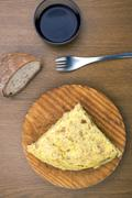 A traditional spanish tapa of spanish omelet with bread, wine and a fork Stock Photos