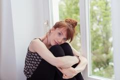 Cute Girl Sitting at the Window Hugging her Knees - stock photo
