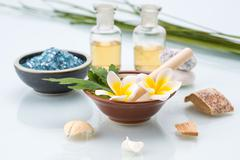 Spa concept with Mortar and Pestle, Flowers, leaf, essential oil, and salt - stock photo