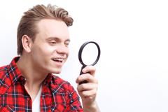 Agreeable guy keeping loupe - stock photo