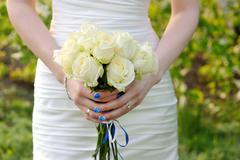 bride holding wedding bouquet of white  roses - stock photo