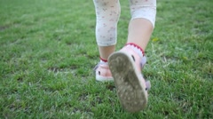 Little girl legs running over a grass in a park during family weekend - stock footage