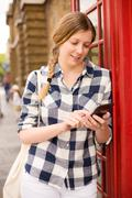 young woman sending a text message in london - stock photo