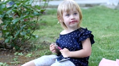 Little girl paints her lips with lipstick of her mom in a park Stock Footage