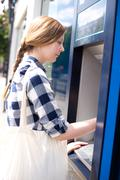 young woman at the atm machine. - stock photo