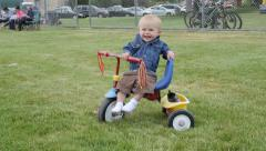Portrait of happy baby smiling on a tricycle. Stock Footage