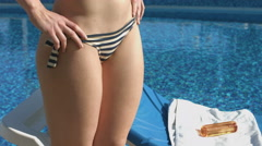 Close look at woman's lower body, sun tanning near the pool Stock Footage