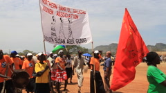 CROWD MARCHES WITH BANNER AT POLITICAL RALLY IN SOUTH SUDAN, AFRICA Stock Footage