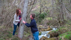 A couple stending near the tree along the creek Stock Footage