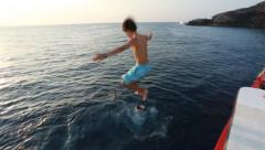 Young male teenager jumping into ocean water - stock footage