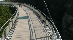 Stock Video Footage of SkyBridge span with glass floor sections, few tourists, camera slide overhead