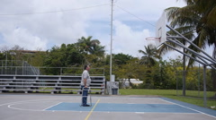 DISABLED-PARAPLEGIC: Old man with walking frame looks at basketball ring 2 Stock Footage