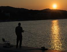 Fisherman chilling out against the beautiful sunset in Greece. - stock photo