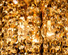 A crystal chandelier shines with golden light Stock Photos