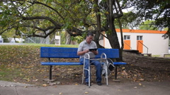 DISABLED-PARAPLEGIC: old man on park bench with Ipad and walking frame stands up Stock Footage