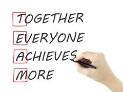 Together Everyone Achieves More written by man's hand Stock Photos