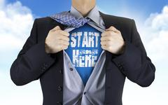 businessman showing Start here words underneath his shirt - stock photo