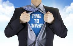 Stock Photo of businessman showing Time to invest words underneath his shirt