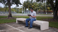 OLD MAN on park bench with Ipad-tablet looks at camera Stock Footage
