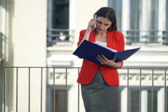 Businesswoman with documents talking on cellphone standing on balconyNTSC Stock Footage