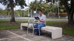 DISABLED-PARAPLEGIC: old man on park bench with Ipad-tablet looks to camera Stock Footage
