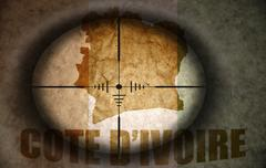 Sniper scope aimed at the vintage ivorian flag and map Stock Illustration